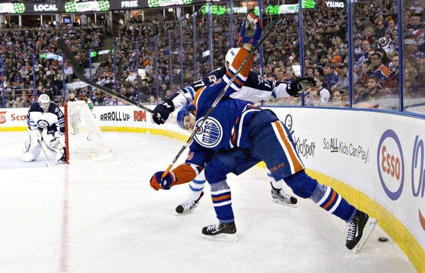 Winnipeg Jets' Adam Lowry (17) trips up Edmonton Oilers' Leon Draisaitl (29) during the second period of an NHL hockey game Saturday, Feb. 13, 2016, in Edmonton, Alberta. (Jason Franson/The Canadian Press via AP)