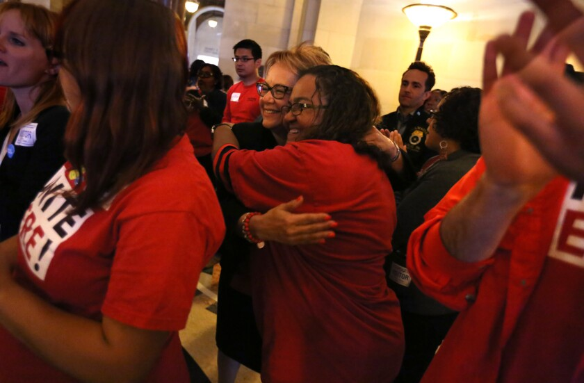 Maria Elena Durazo, president of the national labor organization Unite Here (center left), hugs Alma Romero, a housekeeper for 15 years, while celebrating the L.A. City Council's tentative agreement to raise the city's minimum wage to $15 per hour on May 19.