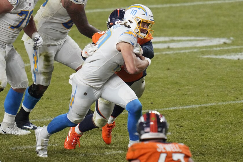 Chargers quarterback Justin Herbert scrambles against the Denver Broncos during the second half Sunday.
