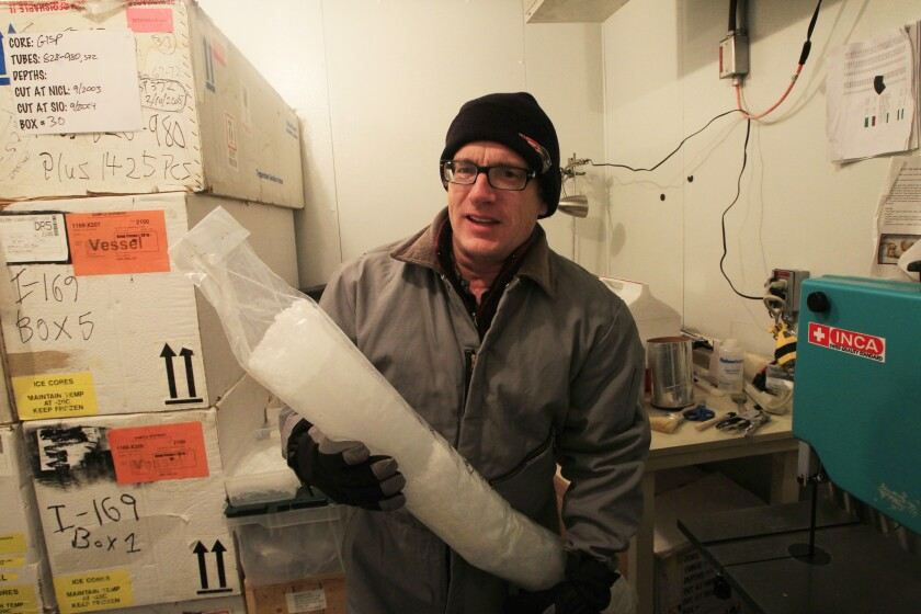 Scripps professor Jeff Severinghaus, bundled up in the storage freezer, holds a long cylinder of ice