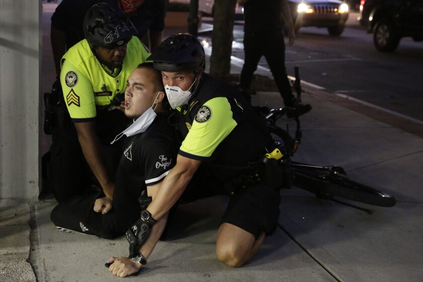 A person is restrained by two police officers on the sidewalk