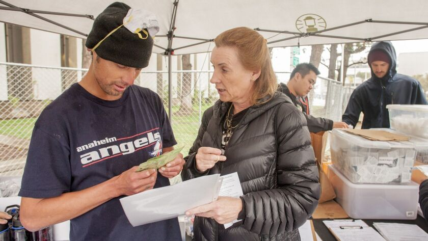 Aimee Dunkle explains a naloxone kit to Robert Salas, who is homeless and living in Santa Ana's Civic Center Plaza. In the background are volunteers Johnny Huynh and Tony Phan.