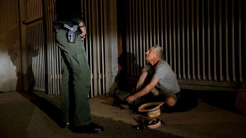 U.S. Border Patrol agent Eduardo Olmos, 38, apprehends a 54-year-old man from Guerrero, Mexico, who