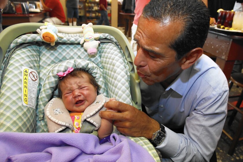 Antonio Villaraigosa greets a baby at Philippe the Original restaurant in Los Angeles in June 2013. The former L.A. mayor is considering running for the U.S. Senate seat being vacated by Barbara Boxer.