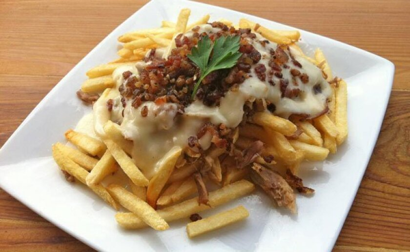 An occasional fries special at Carnitas' Snack Shack: The pulled pork poutine is seasoned french fries, pulled pork, white cheddar gravy and diced bacon.