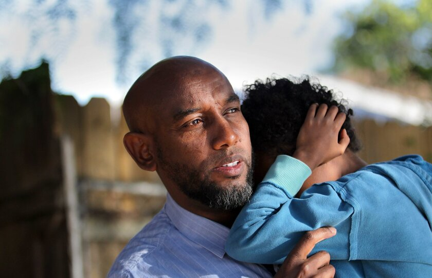 On Wednesday, Liban Ali, left, will receive an award for his efforts to help Somali parents of autistic children. He has first-hand knowlege of what's needed -- two of his five children, including 5-year-old Suhaan Abdi, being held, are autistic.