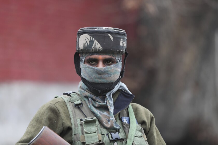 An Indian paramilitary soldier guards as a convoy of New Delhi-based diplomats passes through Srinagar, Indian controlled Kashmir, Thursday, Jan. 9, 2020. Envoys from 15 countries including the United States are visiting Indian-controlled Kashmir starting Thursday for two days, the first by New Delhi-based diplomats since India stripped the region of its semi-autonomous status and imposed a harsh crackdown in early August. (AP Photo/Mukhtar Khan)