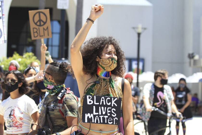 A protester who wanted to be identified as only Kumi joins more then 100 Black Lives Matter protesters