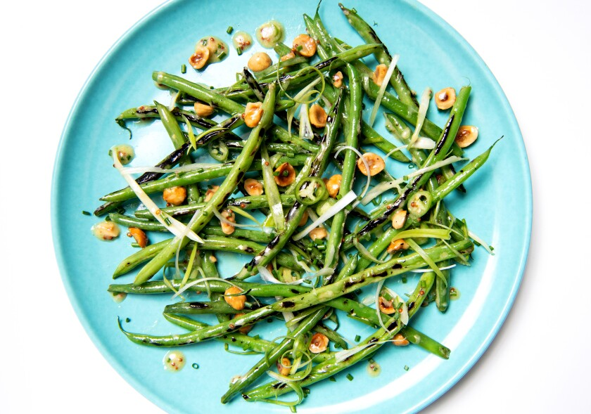 A plate of charred green beans with hazelnuts, scallions and serrano chiles.