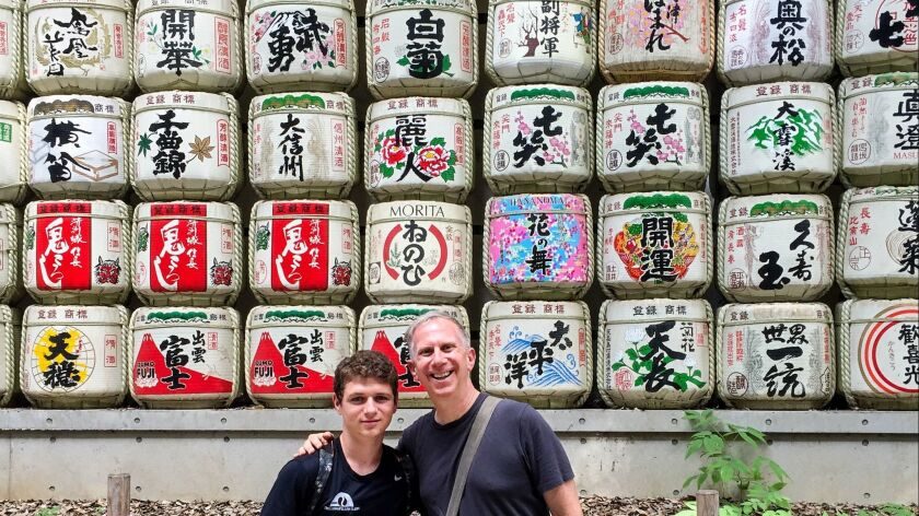 Andrew Bender, Rt, and his nephew Matthew Cohn posing before sake casks wrapped in straw at Meiji Shrine, one of the largest of Japan's native Shinto religion, in Tokyo.