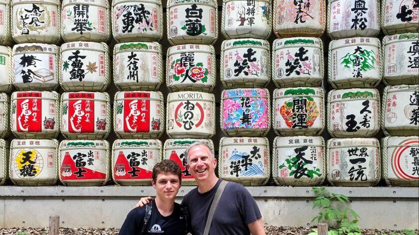 Andrew Bender, Rt, and his nephew Matthew Cohn posing before sake casks wrapped in straw at Meiji Sh
