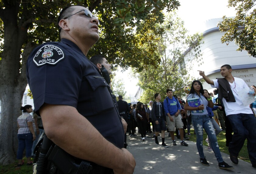 LAUSD police officer Jay Cueva watches as students get out of Manual Arts High School.
