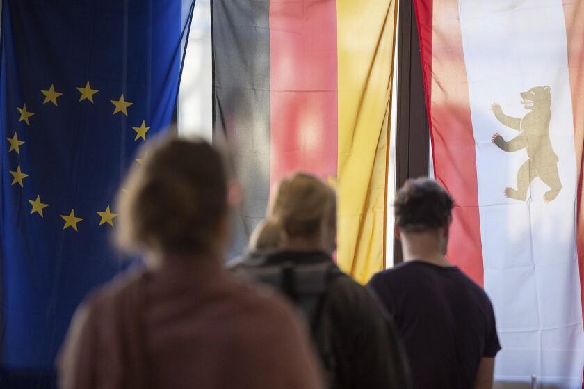 Varios votantes hacen fila ante banderas de Europa, Alemania y Berlín en un centro de votación para depositar sus boletas en Berlín, Alemania, el domingo 26 de septiembre de 2021. Alemania elegía a un nuevo parlamento. (Sebastian Gollnow/dpa via AP)