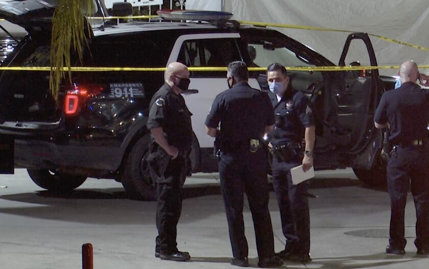 LAPD officers gather at the scene of a shooting.