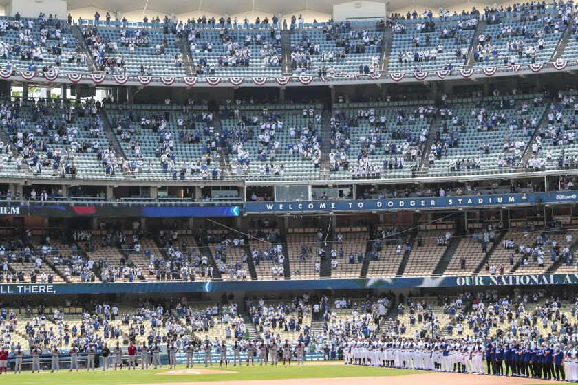 Dodgers and Nationals players line up on the field. Four decks of stadium seating, behind them, are half filled.