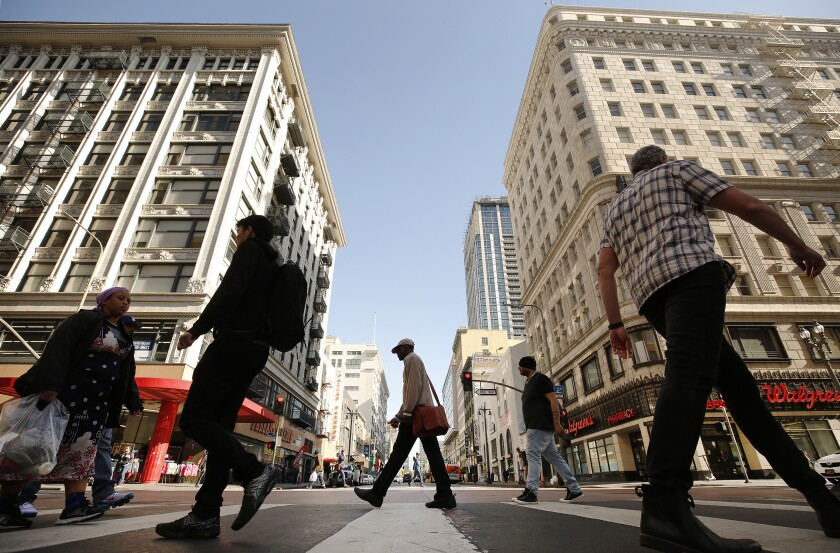 Pedestrians cross Broadway at 5th Street.