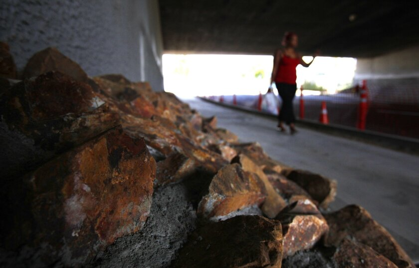A woman walks past riprap that the city recently installed on Imperial Avenue below an Interstate 5 overpass to deter homeless encampments on the street.