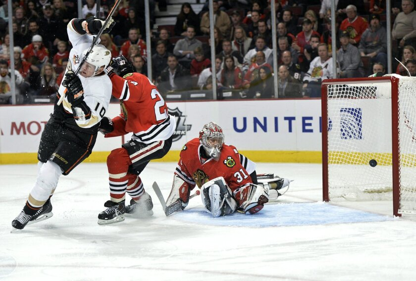 Anaheim Ducks right wing Corey Perry, left, scores past Chicago Blackhawks defenseman Johnny Oduya, center, and goalie Antti Raanta during the first period of an NHL hockey game Friday, Dec. 6, 2013, in Chicago. (AP Photo/Brian Kersey)