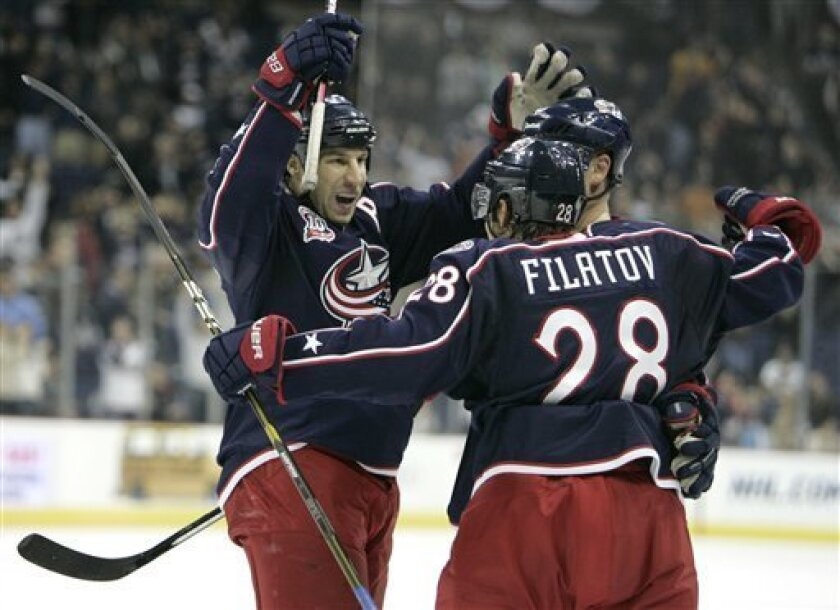 Columbus Blue Jackets' R.J. Umberger, left, celebrates his goal against the St Louis Blues with teammates Jan Hejda, right, of the Czech Republic, and Nikita Filatov, of Russia, in the second period of an NHL hockey game in Columbus, Ohio, Wednesday, Nov. 10, 2010. (AP Photo/Paul Vernon)
