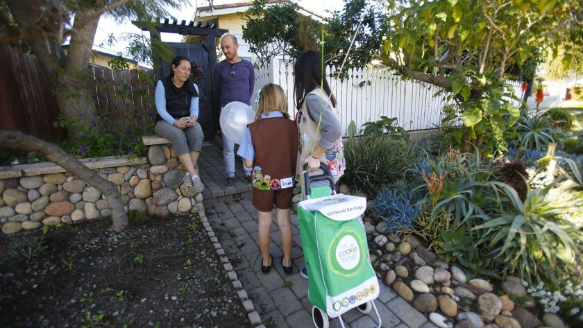 Lilianna Veniegas (right) and Brownie Girl Scout Zeya Cavanaugh sell a few boxes of cookies to Gonza