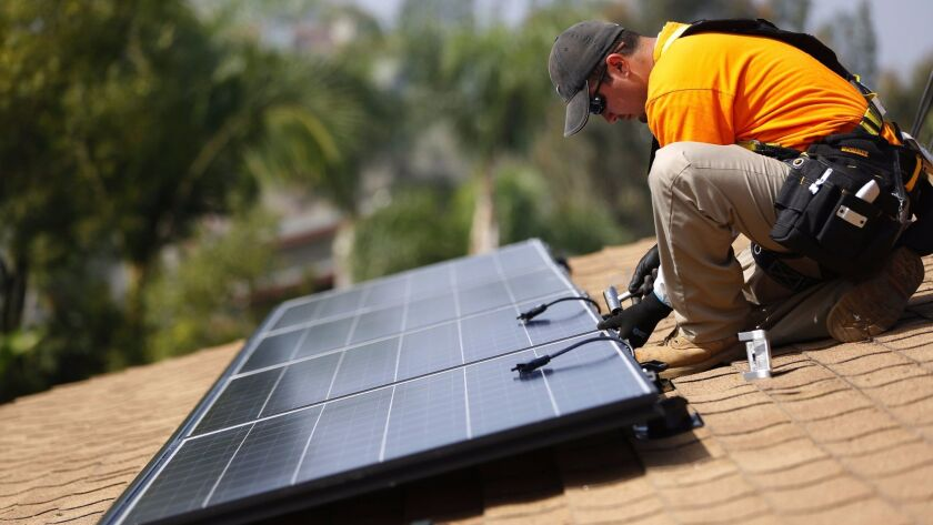 Vivint Solar technician Eduardo Aguilar installs solar panels on the roof of a house in Mission Viejo.