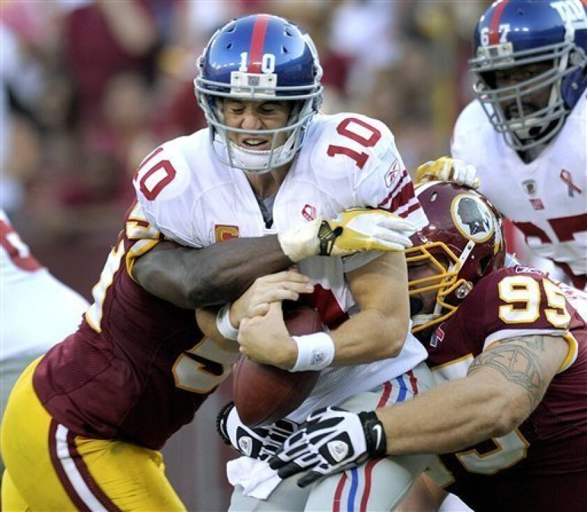 New York Giants quarterback Eli Manning is sacked by Washington Redskins linebacker London Fletcher, left, and nose tackle Chris Neild, right, during the second half of an NFL football game on Sunday, Sept. 11, 2011, in Landover, Md. (AP Photo/Susan Walsh)