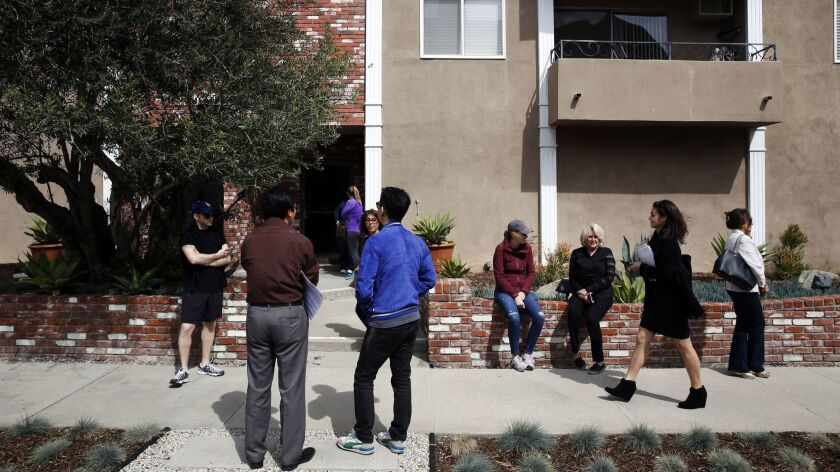 People wait outside to tour a condo for sale on South Bentley Avenue during an open house on Sunday,
