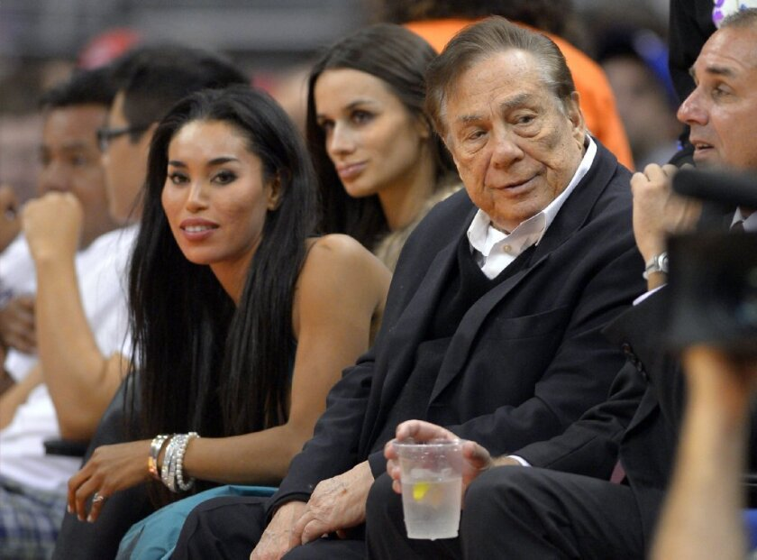 V. Stiviano, left, sits next to Clippers owner Donald Sterling as they watch the Clippers play the Sacramento Kings in Los Angeles last fall.