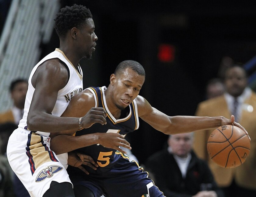 Utah Jazz guard Rodney Hood (5) works against New Orleans Pelicans guard Jrue Holiday during the first half of an NBA basketball game in New Orleans, Wednesday, Feb. 10, 2016. (AP Photo/Tyler Kaufman)