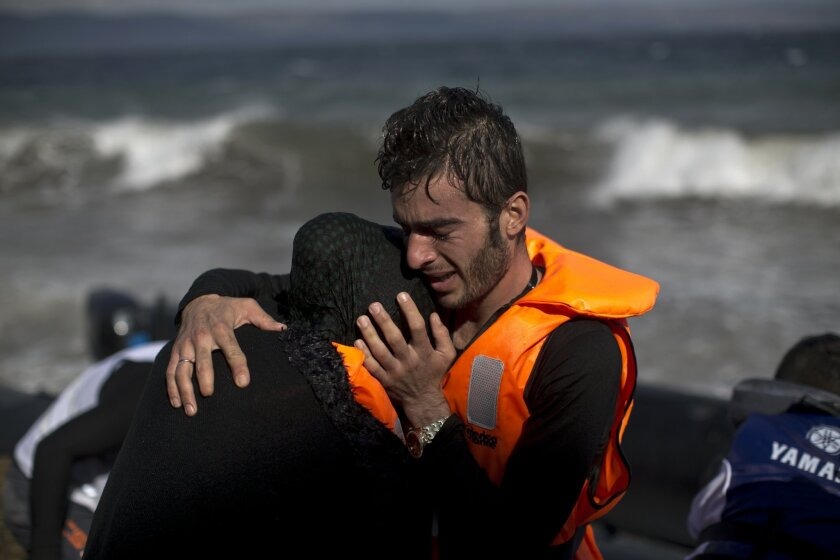 A man embraces his wife after they arrived by boat at a beach on the northern coast of Lesbos, Greece, Saturday, Oct. 31, 2015. An official leading rescue efforts on the Greek island of Lesbos has warned that the death toll in the eastern Aegean Sea is likely to rise in the coming days unless urgen