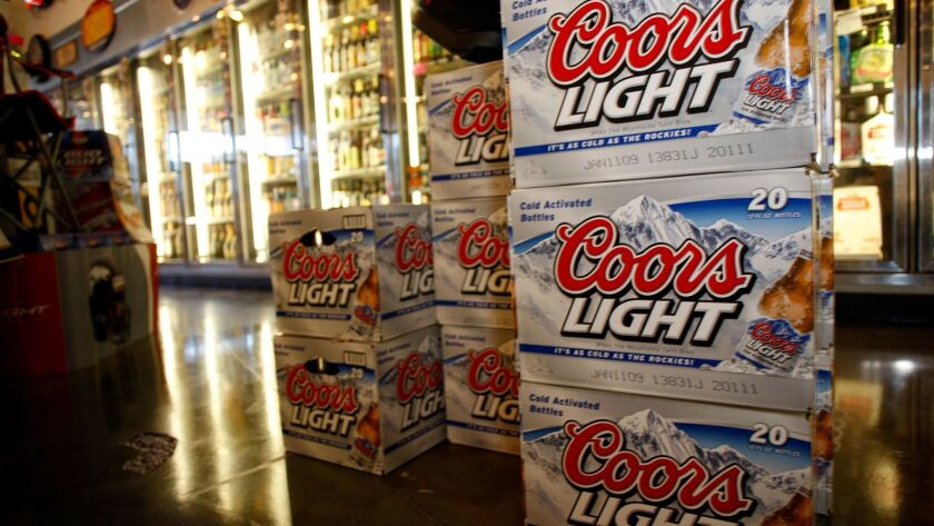 Packages of Coors Light are on display in front of coolers in a liquor store in southeast Denver on