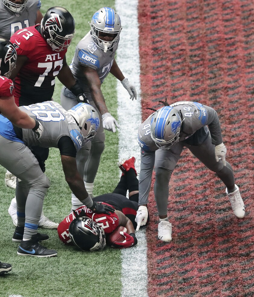 Detroit Lions players point at the football held by Atlanta Falcons' Todd Gurley during the fourth quarter of an NFL football game Sunday, Oct. 25, 2020, in Atlanta. Gurley saw a tantalizing path to the end zone and couldn't help himself. He tried to fall down, but it was too late. Gurley landed on the goal line for a touchdown that, as it turned out, led to another stunning loss for the Atlanta Falcons. (Curtis Compton/Atlanta Journal-Constitution via AP)