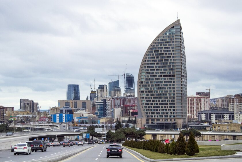 FILE - In this Feb. 19, 2016, file photo, The Trump International Hotel, the highest building, is seen in Baku, Azerbaijan. Just six months before he launched his presidential campaign, Donald Trump announced a new real estate project in Baku. The partner: the 35-year-old son of an Azerbaijani mini
