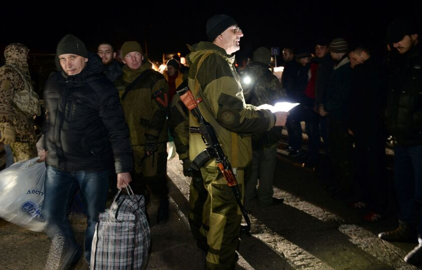 Armed supporters of the self-declared People's Republic of Donetsk oversee their end of a prisoner exchange with the Ukrainian government on Friday.