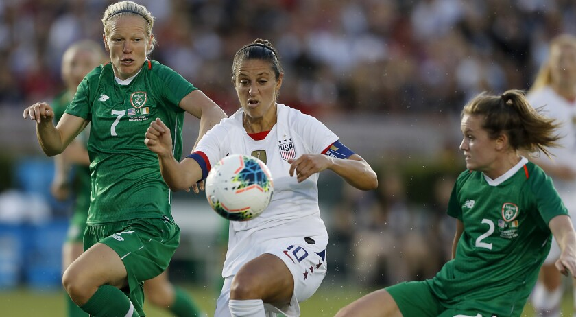 U.S. forward Carli Lloyd tries to control the ball between Ireland's Diane Caldwell, left, and Heather Payne.