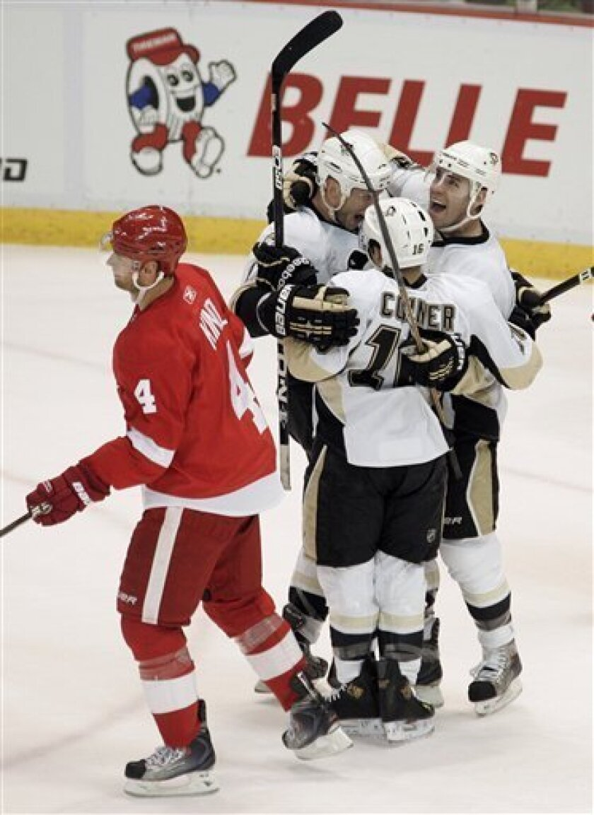 Pittsburgh Penguins' Pascal Dupuis, right, celebrates his goal with teammates Chris Conner (16) and Jordan Staal as Detroit Red Wings' Jakub Kindi (4), of the Czech Republic, skates away in the first period of an NHL hockey game Monday, March 21, 2011, in Detroit. (AP Photo/Duane Burleson)