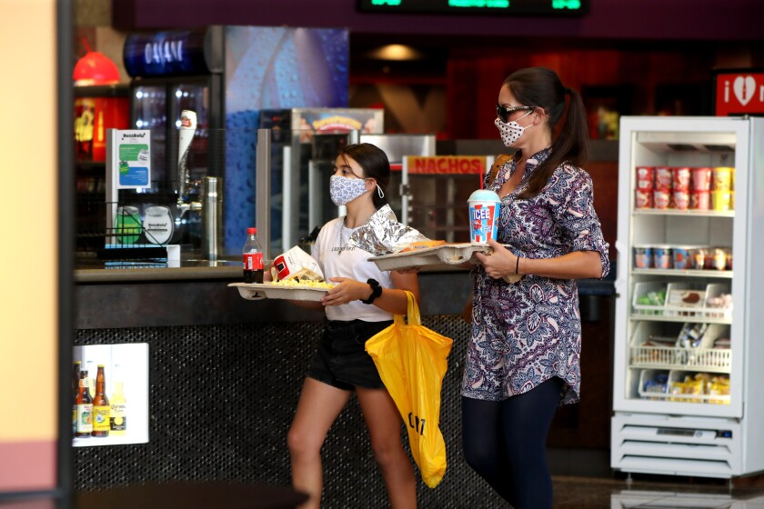 Moviegoers wearing masks grab snacks at the just reopened Cinemark Century Cinema in Huntington Beach on Friday.