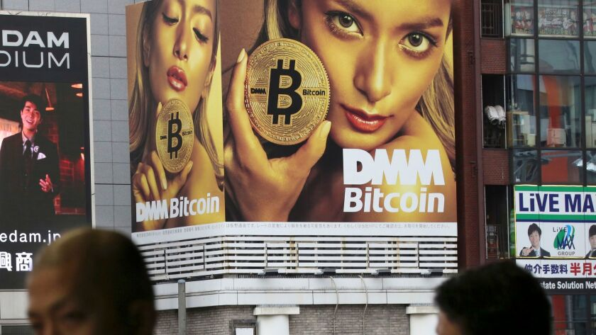 A huge advertisement for bitcoin is displayed near a train station in Tokyo. Bitcoin and other cryptocurrencies offer shadowy tales for writers and filmmakers.
