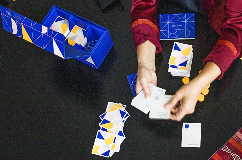 Hands hold cards above a table holding more cards and a box