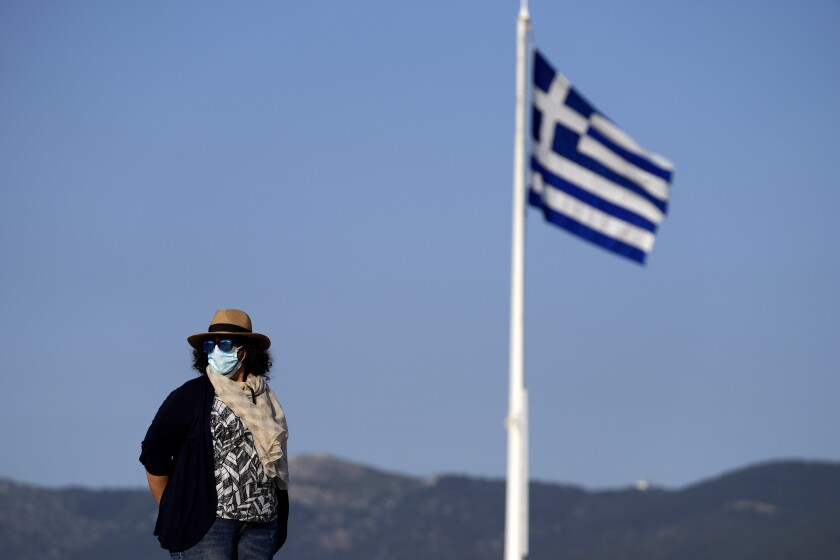 An employee of the Acropolis hill wearing protective face mask stands guard next of a Greek flag during a media tour for the Foreign Correspondents organised by the Greek Cultural Ministry at the Acropolis hill in Athens, Tuesday, June 8, 2021. Following last year's COVID-19 travel restrictions, tourism-reliant Greece is hoping to see a significant uptick in tourist arrivals this summer, and has expanded its list of nationalities allowed in for non-essential travel to include 23 countries – among them the U.S., the U.K. and China – as well as members of the European Union and the Schengen passport-free travel zone. (AP Photo/Thanassis Stavrakis)