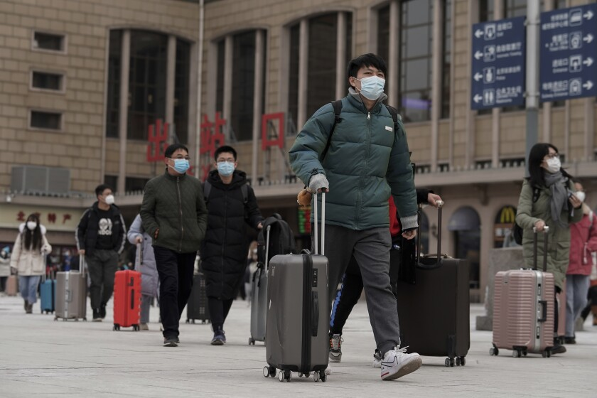 Arriving passengers in masks walk out of a Beijing railway station Tuesday.