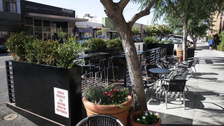 "San Diego's first ""Parklet,"" a public hangout with tables, chairs and shade made out of two former parking spaces in front of Caffe Calabria in North Park. (Sean M. Haffey)"