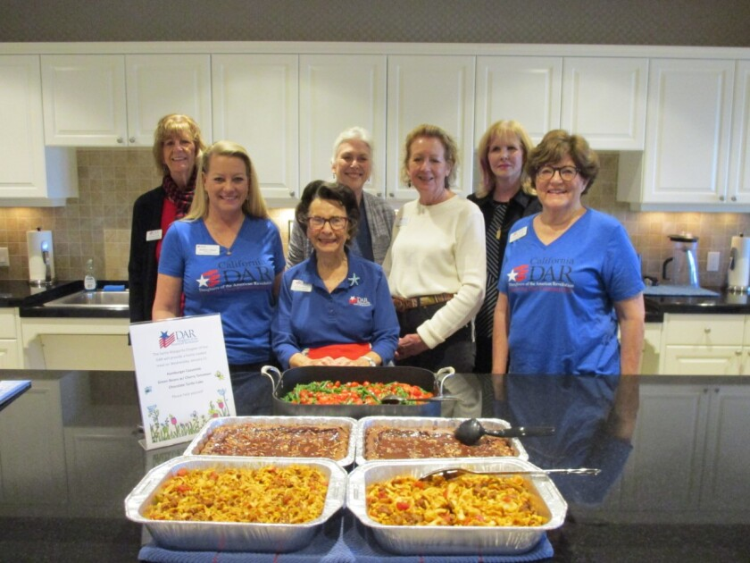 Six members of the Santa Margarita Chapter, Daughters of the American Revolution, joined by Kris Wood, National Chair DAR Service to Veterans Committee, met at Fisher House on Camp Pendleton to cook lunch for the residents, which the group does several times a year, led by member Linda Ramos. Fisher House is a home away from home for military personnel receiving services at the Naval Hospital on base. In addition to the meals, chapter members donate bottled water, computer items, cleaning supplies, toiletries, hot pads and towels for the kitchen along with frozen meals. From left, serving at Fisher House, Alida Woodward, Kris Wood, Wanda Prosser, Jacquie Berzins, Janet Giovannetti, Linda Ramos and Charla Boodry. Visit santamargarita.californiadar.org.