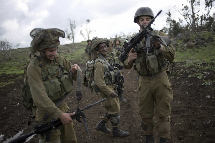 Israeli soldiers of the Golani brigade adjust their weapons during training near the border with Syria in the Israeli-controlled Golan Heights, Wednesday, Feb. 26, 2014. Hezbollah says Israel carried out an airstrike targeting its positions in Lebanon near the border with Syria earlier this week, c