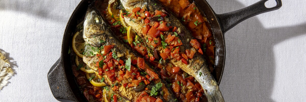 Roasted fish with tomatoes and olives in a pan.