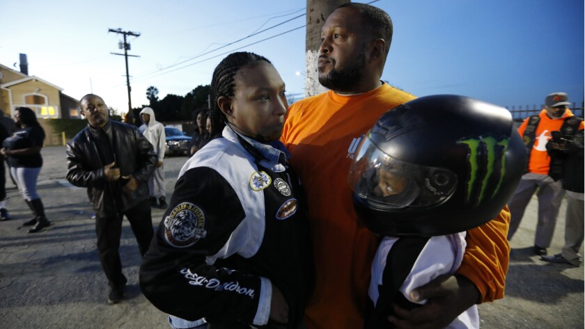 Eric Metoyer holds Kia Metoyer (L) and 12-year-old Emerie Metoyer as they attend a vigil near Nates Liquor Mart in Compton.
