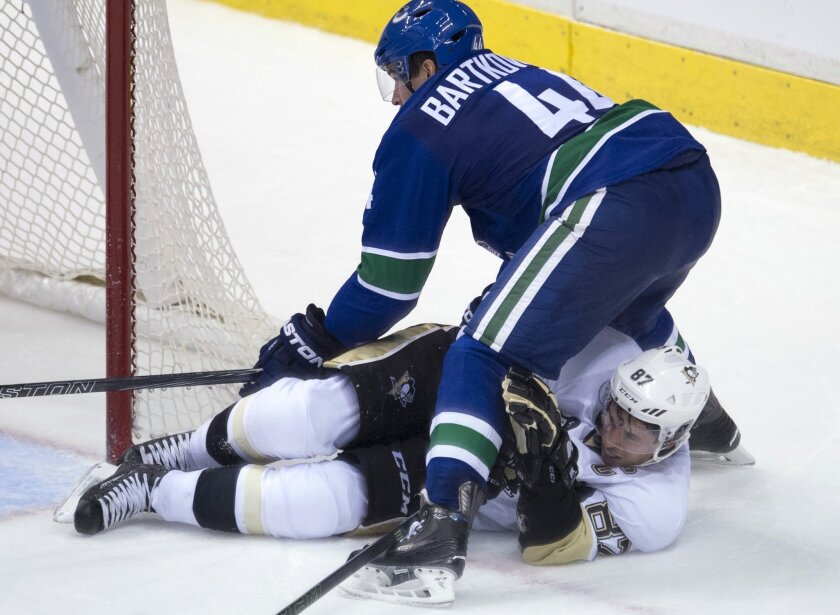 Pittsburgh Penguins center Sidney Crosby (87) vies for control of the puck with Vancouver Canucks defenseman Matt Bartkowski (44) during the third period of an NHL hockey game Wednesday, Nov. 4, 2015, in Vancouver, British Columbia. (Jonathan Hayward/The Canadian Press via AP)