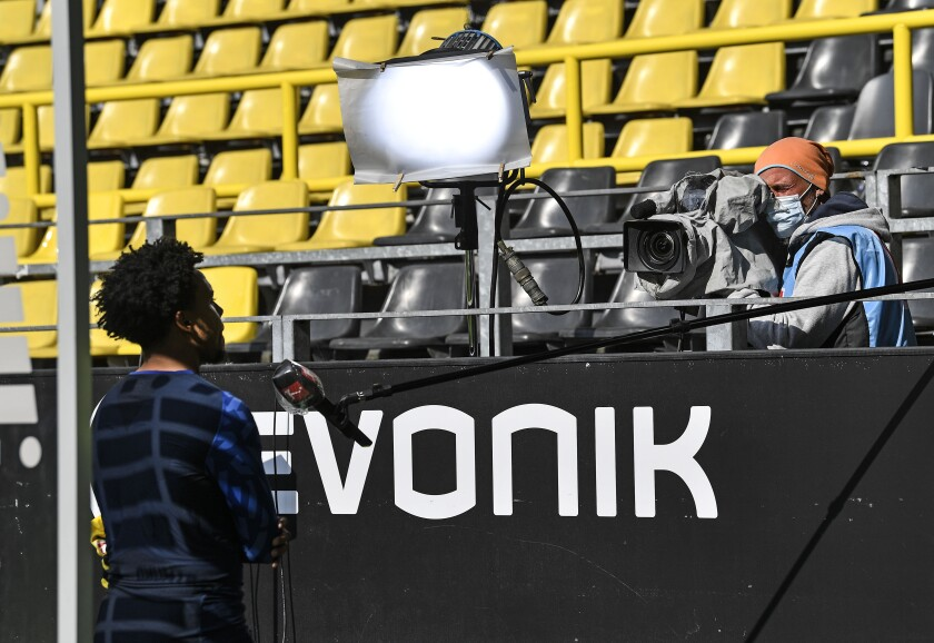 Schalke's Weston McKennie gives an interview beside the pitch with distance to the camera after the German Bundesliga soccer match between Borussia Dortmund and Schalke 04 in Dortmund, Germany, Saturday, May 16, 2020. The German Bundesliga becomes the world's first major soccer league to resume after a two-month suspension because of the coronavirus pandemic. (AP Photo/Martin Meissner, Pool)
