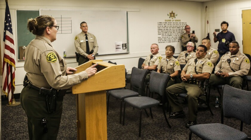 Cmdr. Coronne Jacob gives a briefing, attended by some volunteer reserve deputies, at the Los Angeles County Sheriff's Department's Industry Station.