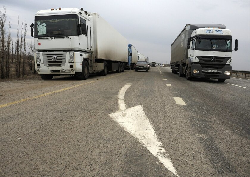 Several trucks stand on the sidelines as another drives past to take part in a demonstration, on the outskirts of Moscow outside Volgograd, Russia, Sunday, Nov. 29, 2015. Russian truck drivers have been protesting across the country, and one of their leaders says hundreds of trucks are now heading toward Moscow to press their demands. The truck drivers, many of whom own and operate their own vehicles, are protesting the introduction of a hefty road tax for long-distance haulers. (AP Photo/Dmitry Rogulin)